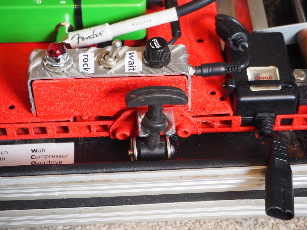 Switch and rubber catch on side of guitar pedal board